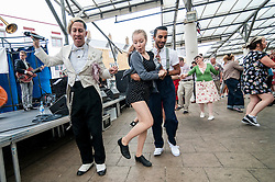 © Licensed to London News Pictures. 28/06/2015. London, UK. Natty Congeroo (L) and members of the public dancing at the Swing East jump 'n' jive jamboree in Chrisp Street Market in London's East End.  Revellers gathered together in vintage clothing to celebrate fifties music and dance, lots and lots of dance. Photo credit : Stephen Chung/LNP