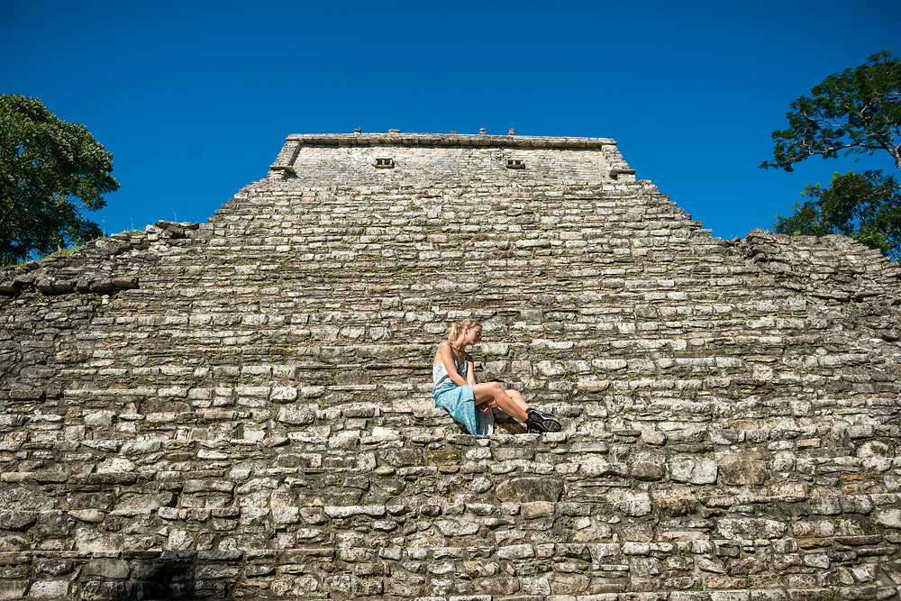 Palenque, Mexico - November 24, 2014: Chloe, from Australia, sits on the stone steps at the Temple of the Count in Palenque, Mexico. The Mayan city flourished in the 7th century.