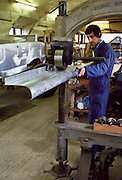 Man rolling an aluminium panel during the restoration of a rare vintage Rolls Royce, Gloucestershire, UK.
