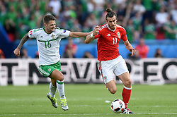 Gareth Bale of Wales battles for the ball with, Oliver Norwood of Northern Ireland  - Mandatory by-line: Joe Meredith/JMP - 25/06/2016 - FOOTBALL - Parc des Princes - Paris, France - Wales v Northern Ireland - UEFA European Championship Round of 16