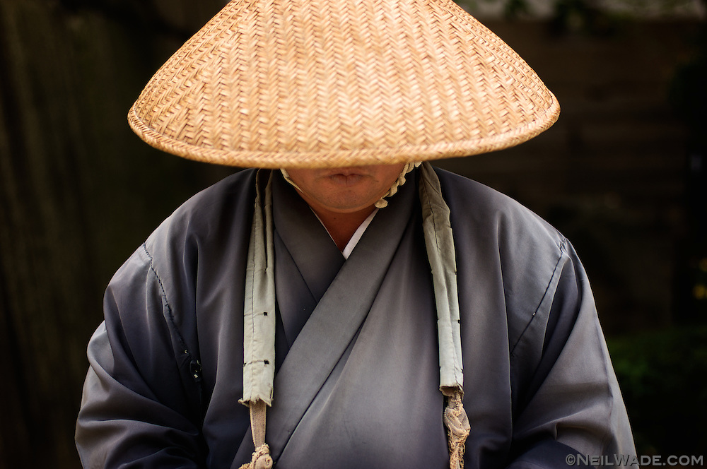 A Japanese Buddhist monk quietly chants while accepting donations outside an Osaka, Japan castle.