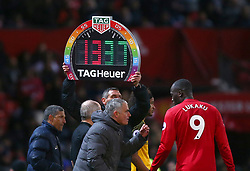 The fourth official holds up a rainbow board as Manchester United manager Jose Mourinho talks to Manchester United's Romelu Lukaku