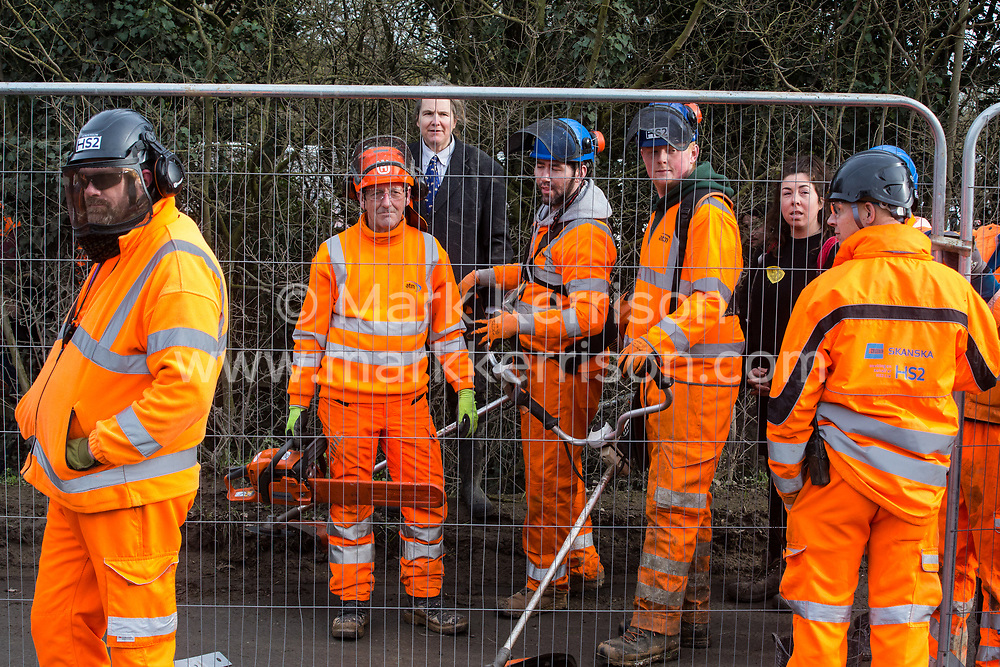 Harefield, UK. 8 February, 2020. Environmental activists seek to prevent HS2 engineers from using a chainsaw and strimmers to carry out tree felling works for the high-speed rail project alongside Harvil Road in the Colne Valley. The activists, based at a series of wildlife protection camps in the area, prevented the tree felling, for which road and rail closures had been implemented, for the duration of the weekend for which it had been scheduled.