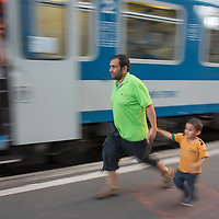Illegal migrant man and boy rush to get on their train to travel to Germany at the main railway station Keleti in Budapest, Hungary on August 31, 2015. ATTILA VOLGYI