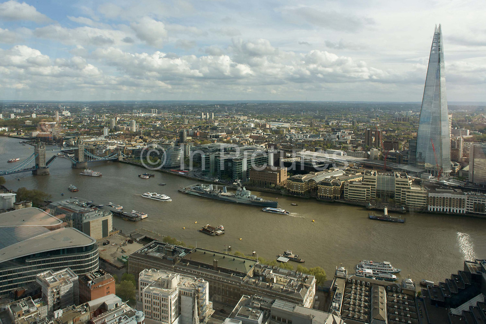 River Thames and southbank London skyline (The Shard, right) seen from the Sky Garden of the Walkie Talkie building in the City of London. The panoramic cityscape shows the modern metropolis looking south-eastwards, from the northern bank of the river to the southern where the borough of Southwark starts, continuing into the distance. On the river is the WW2 battleship museum HMS Belfast and Tower Bridge, a Victorian crossing built in 1894. The Shard is an 87-storey skyscraper standing 306 metres (1,004 ft) high.