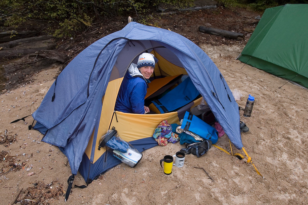 A woman packs up her tent during a sea kayaking trip in Lake Superior Provincial Park near Wawa Ontario Canada.