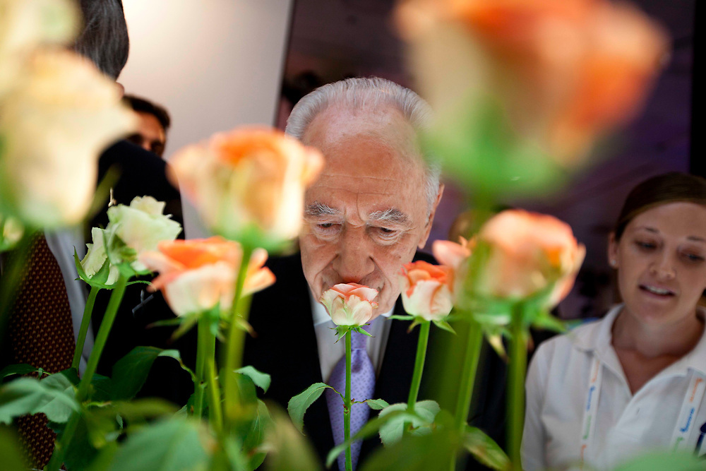Israel's President Shimon Peres (C) smells flowers at an exhibition presented during the Israeli Presidential Conference in Jerusalem on June 23, 2011.