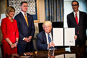 Rep. Claudia Tenney, R-N.Y., Sen. David Perdue, R-Ga., and Treasury Secretary Steven Mnuchin look in as President Donald Trump hold up one of the  directives he signed on tax and Wall Street regulations in Washington, District of Columbia, U.S., on Friday, April 21, 2017. This was President Trump's first visit to the Treasury Department.