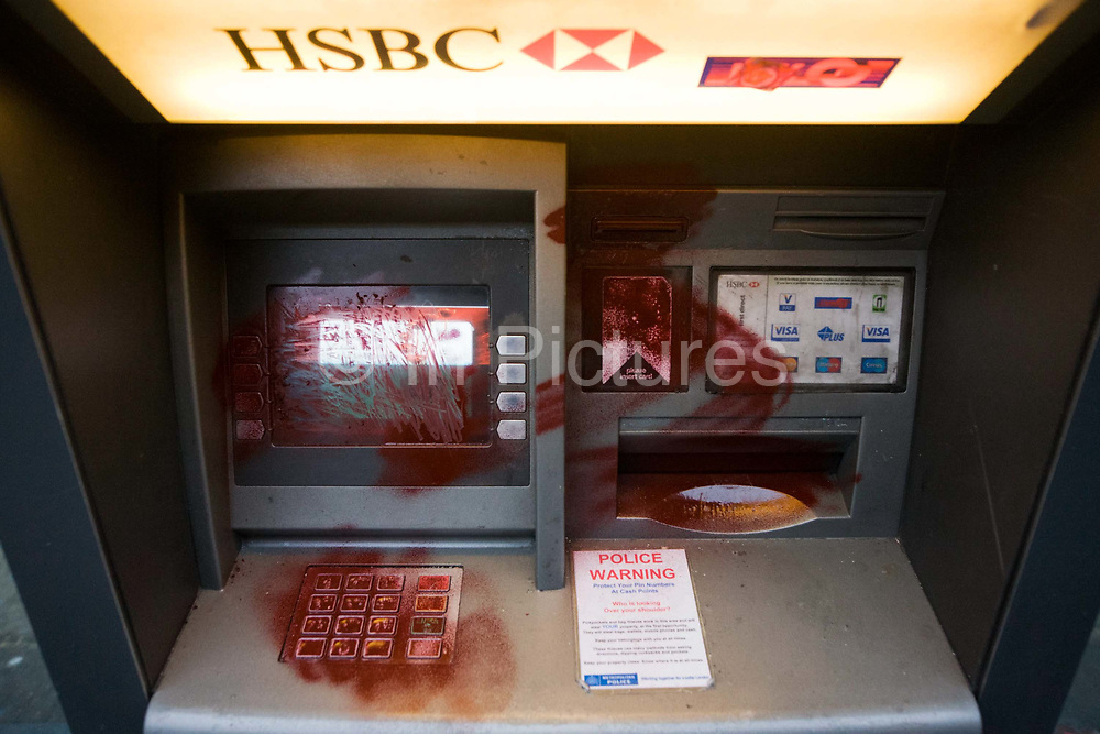 Vandalism to a tax-evading HSBC bank dispenser the morning after the TUC-organised anti-government cuts to Britain's economy. Aerosol has been sprayed on the keypad, the screen and slot during a day's rioting by anarchists who broke away from a largely peaceful protest agasinst government economic cuts. Organisers estimated between 250,000 and 500,000 people took part but police said a total of 201 arrests had been made during the day largely for a variety of public order offences, they said. In addition, 66 people were reported to have been injured, including at least 31 police officers, 11 of whom required hospital treatment.
