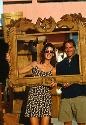 Couple holding up an empty wooden frame smiling and being playful