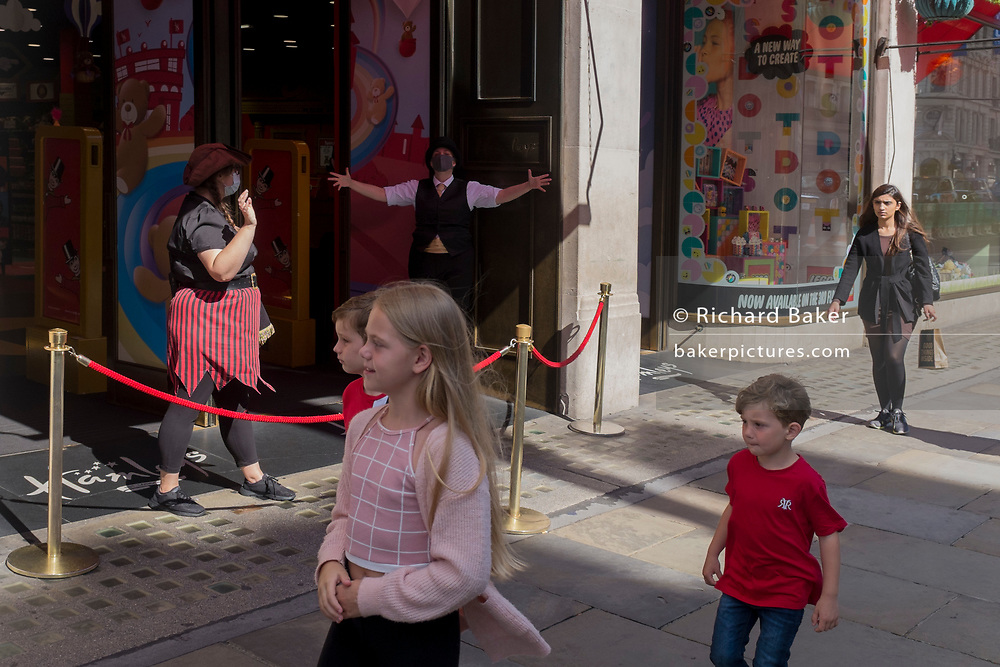 With a further 89 UK covid victims in the last 24hrs, bringing the total victims to 43,995 during the Coronavirus pandemic, shops like Hamleys continue opening along London's Regent Street where childrens' entertainers again provide theatrical action for passing kids, on 2nd July 2020, in London, England.