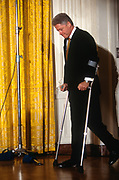 WASHINGTON, DC, USA - 1997/04/02: U.S. President Bill Clinton arrives using crutches for a Roundtable Discussion on Education event in the East Room of the White House April 2, 1997 in Washington, DC.  Clinton is using crutches following knee surgery.   (Photo by Richard Ellis)