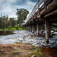 Water running over the rocks under a road bridge in a small WA country town.