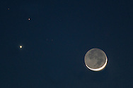 Goshen, New York - The crescent moon and the planets Venus, lower left, and Mars, upper left, shine in the twilight sky on Feb. 20,  2015.