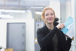 Smiling female worker removing file from cabinet