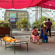 1 May 2021<br /> <br /> Indirapuram, Gazhiabad<br /> Relatives of a deceased woman sit in the 40 degrees heat next to her covered deceased body waiting for the arrival of a ambulance to transport the victim. As a result of the situation,  ambulances are very few and one could only be arranged nearly three hours after she was had stopped breathing.