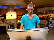 A young man looks at computers in a campus bookstore.