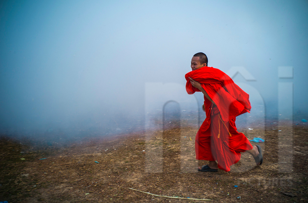 A joyfull buddhist monk runs in front of a launching ramp  during Boun Bang Fai, aka Rocket Festival, Ban Don Nieng, a small village near Vientiane, Laos, Southeast Asia