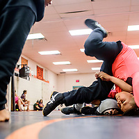 Shawn Torres, right, flips Nikcolii Torres onto his back under the guidance of a Gallup Bengal wrestler during the Gallup Wrestling Camp at Gallup High School Thursday.