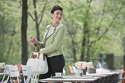 Mature woman with handbag and looking over shoulder in the sidewalk cafe, Bavaria, Germany