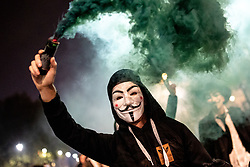 © Licensed to London News Pictures. 05/11/2018. London, UK. A demonstrator lights a flare as he takes part in the Million Mask March, an anti-capitalist protest organised by Anonymous UK. The march takes place on bonfire night, the anniversary of Guy Fawkes' plot to blow up the Houses of Parliament with gunpowder. Photo credit : Tom Nicholson/LNP