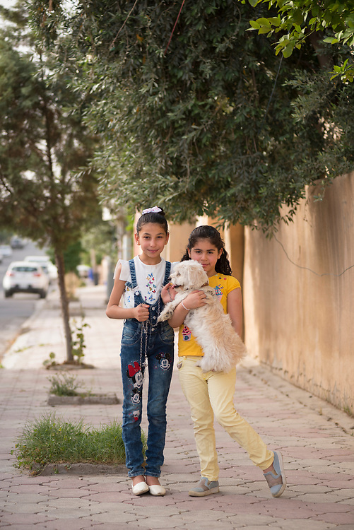 Erbil, Iraq - May 15, 2017: Two friends, one Muslim and one Christian, enjoy a walk together in Ankawa, on the outskirts of Erbil. Samara, in yellow shirt, is age 8 and from Kirkuk. Laren is age 10. And the dog, they told me, is Nano, age 6.