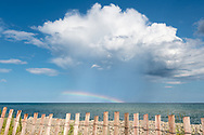 A stormcloud wears a rainbow as it drifts across the horizon over Lake Huron.