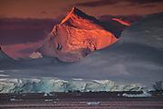 Alpenglow lights up high peaks on Wiencke and Anvers Islands behind Port Lockroy, Antarctic Peninsula