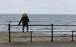 © Licensed to London News Pictures. 01/06/2013<br /> <br /> Saltburn, Cleveland, United Kingdom<br /> <br /> A woman sits on railings on the lower promenade on a cloudy first day of summer on the beach at Saltburn by the sea in Cleveland.<br /> <br /> Photo credit : Ian Forsyth/LNP