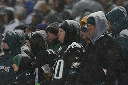 A Philadelphia Eagles fan holds a beer and looks on from the stands in the snow during the NFL game between the Detroit Lions and the Philadelphia Eagles on Sunday, December 8th 2013 in Philadelphia. (Photo by Brian Garfinkel)
