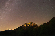 Meteors rain over Seneca Rocks as the northern band of the Milky Way and Andromeda Galaxy hangs above a star rich sky.