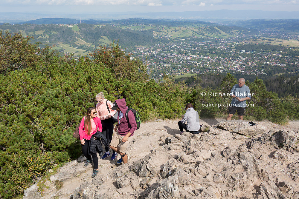 High above the southern Polish mountain resort of Zakopane, hikers climb near the top of Sarnia Skala, a mountain in the Tatra National Park, on 16th September 2019, near Koscielisko, Zakopane, Malopolska, Poland.