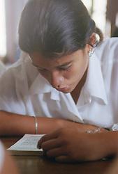 Secondary school girl reading book at desk,