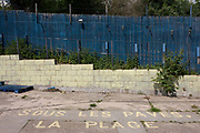"Abandoned and derelict premises at the rear of a former garden centre business, due soon for redevelopment. On the ground are the words ""Sous les paves, la plage"" - in the French language. This roughly translates as 'under the pavement, the beach', a clue to the land's former use as a garden and plant centre followed by a pop-up artists' studio. The property is now vacant, awaiting development for a future library, apartments and small supermarket. Blue panelled fencing borders the premises and faded yellow breeze blocks separate weeds."