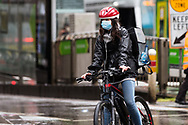 A young woman wearing a mask is seen riding her bike in the CBD during COVID-19 in Melbourne, Australia. Victoria has recorded 14 COVID related deaths including a 20 year old, marking the youngest to die from Coronavirus in Australia, and an additional 372 new cases overnight. (Photo by Dave Hewison/Speed Media)