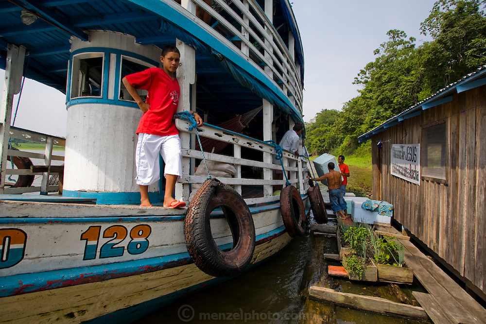 A boy stands on the deck of a river boat that has stopped alongside the floating home of João Agustinho Cardoso, a fisherman who lives on a branch of the Solimoes River 6 hours upstream from the town of Manacapuru, in the state of Amazonas, Brazil.   (João Agustinho Cardoso is featured in the book What I Eat: Around the World in 80 Diets.)