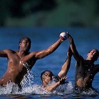 USA, Washington, Seattle, Young men play football in Lake Washington in Seward Park on summer afternoon