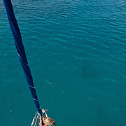 Ren C. leans against the headstay and mainsail as seen from above after wrapping the sail off Glovers Reef on the coast of Belize.