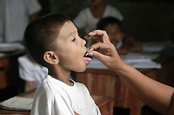 Aung Kyaw Kyaw   (8)receives a deworming tablet and then takes a drink of water as part of a nationwide programme for schoolchildren in the Primary School in Laputtaloke Taung village close to Lamputta, Myanmar.