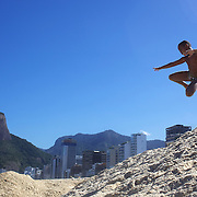 Local youngsters play on a sand hill on Ipanema beach, Rio de Janeiro,  Brazil. 5th July 2010. Photo Tim Clayton..
