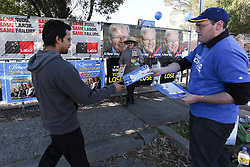 © Licensed to London News Pictures. 7/9/2013. Australian voter gets handed a 'how to vote' card by a Liberal volunteer in the electorate of Bruce during the Australian Federal Election. Photo credit : Asanka Brendon Ratnayake/LNP