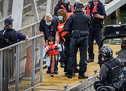 © Licensed to London News Pictures. 25/07/2021. Dover, UK. A young migrant is helped ashore by Border Force officers at Dover Harbour in Kent after crossing the English Channel. Hundreds of migrants have made the crossing in the calm weather this week. Photo credit: Stuart Brock/LNP
