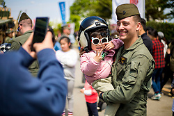 U.S. Marine Corps Cpl. Gage Bellamy, a helicopter crew chief with Marine Heavy Helicopter Squadron-465, Marine Aircraft Group-16, 3rd Marine Aircraft Wing, holds a child for a photo during the 70th anniversary of the City of Pohang Cultural Festival Apr. 27, 2019 in Pohang, South Korea. U.S. Marines displayed tactical vehicles alongside Republic of Korea Marines, allowing the local community to see the relationship between the U.S. and R.O.K. Marine Corps. (U.S. Marine Corps Photo by Lance Cpl. Nicole Rogge)
