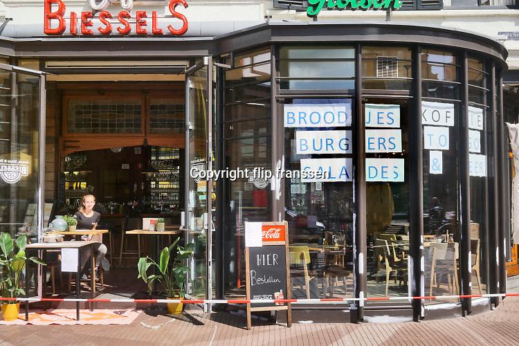 Nederland, Nijmegen, 30-4-2020 De horeca is al enkele weken gesloten vanwege de coronadreiging en veel ondernemers willen dat de regering het normale dagelijks leven weer langzaam laat opstarten . Deze horecagelegenheid, cafe, lunchcafe, biedt de mogelijkheid broodjes te bestellen en af te halen . Afhalen,take,away,creatief,creatieve,oplossing, Opgestapelde stoelen . Unlock,beperkende,beperkingen, opheffen,versoepelen,versoepeling , opengooien, open, geopend . Foto: Flip Franssen