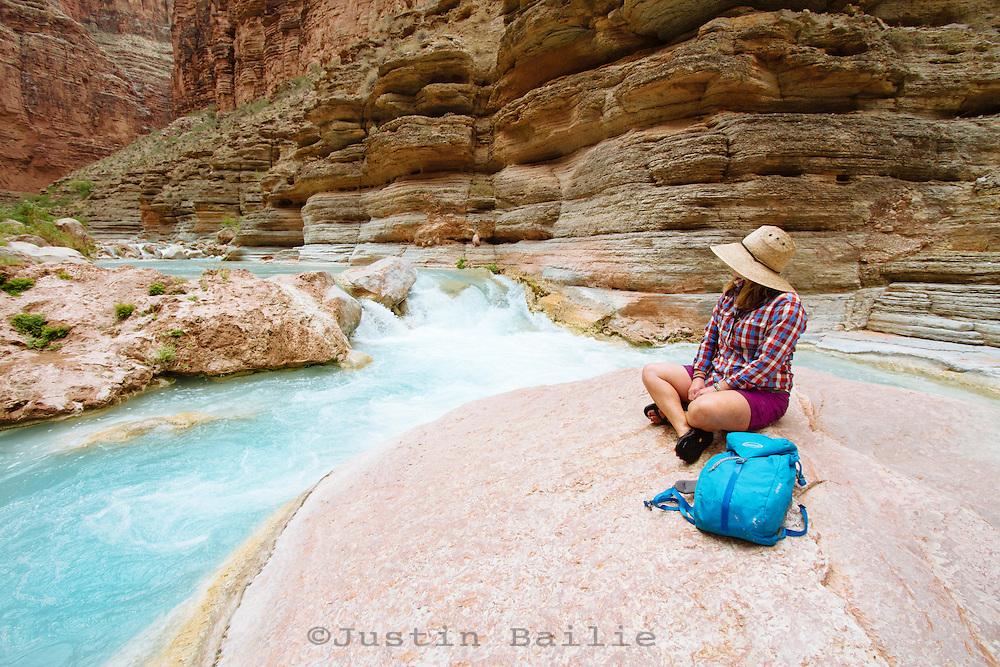 Young woman hiking up Havasu Creek while on a raft trip down the Grand Canyon National Park, AZ.