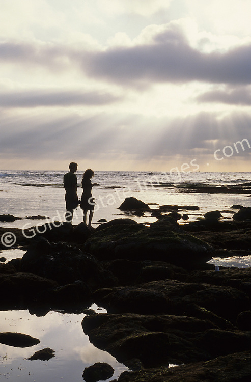 A couple in silhouette on the beach