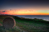 Taken in the country near the small town of Grancamp-Maisy, is a sunset scene of a field with a hay bale in the foreground and the ocean in the background.