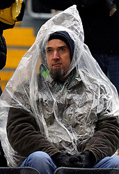 A fan shelters from the rain under a poncho in the Graham Hughes stand during the Premier League match at Molineux, Wolverhampton.