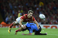 Liam Williams of Wales gets a knock in a tackle from Uruguay's Rodrigo Silva. .Rugby World Cup 2015 pool A match, Wales v Uruguay at the Millennium Stadium in Cardiff, South Wales  on Sunday 20th September 2015.<br /> pic by  Andrew Orchard, Andrew Orchard sports photography.