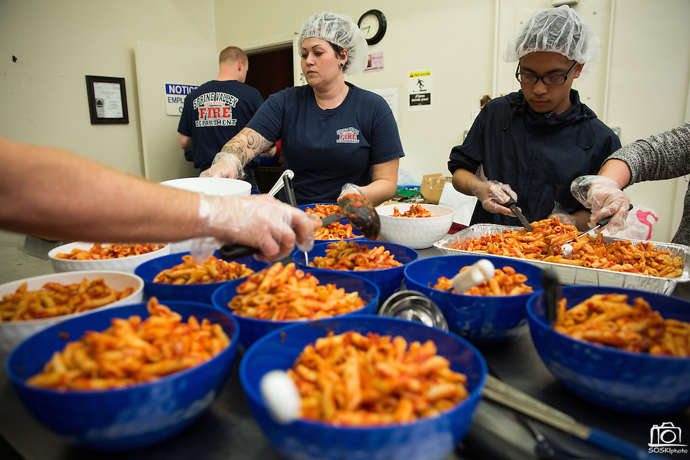 Members of the Spring Valley Volunteer Fire Department prepare pasta, french bread, salad, and buckets of crab during the Milpitas Chamber of Commerce 21st Annual Auction & Crab Feed at Napredak Hall in San Jose, California, on March 7, 2014. (Stan Olszewski/SOSKIphoto)
